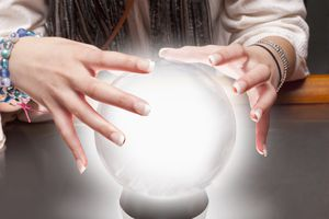 Hands hovering over a crystal ball