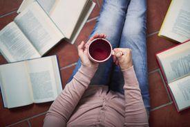 Person with mug sitting among books.