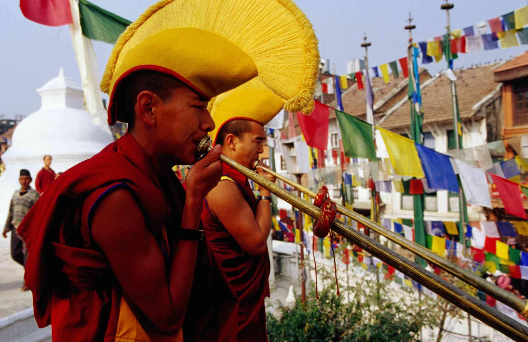 Tibetan Buddhist monks sound long horns to begin Losar observance at Bodhnath Stupa, Nepal.