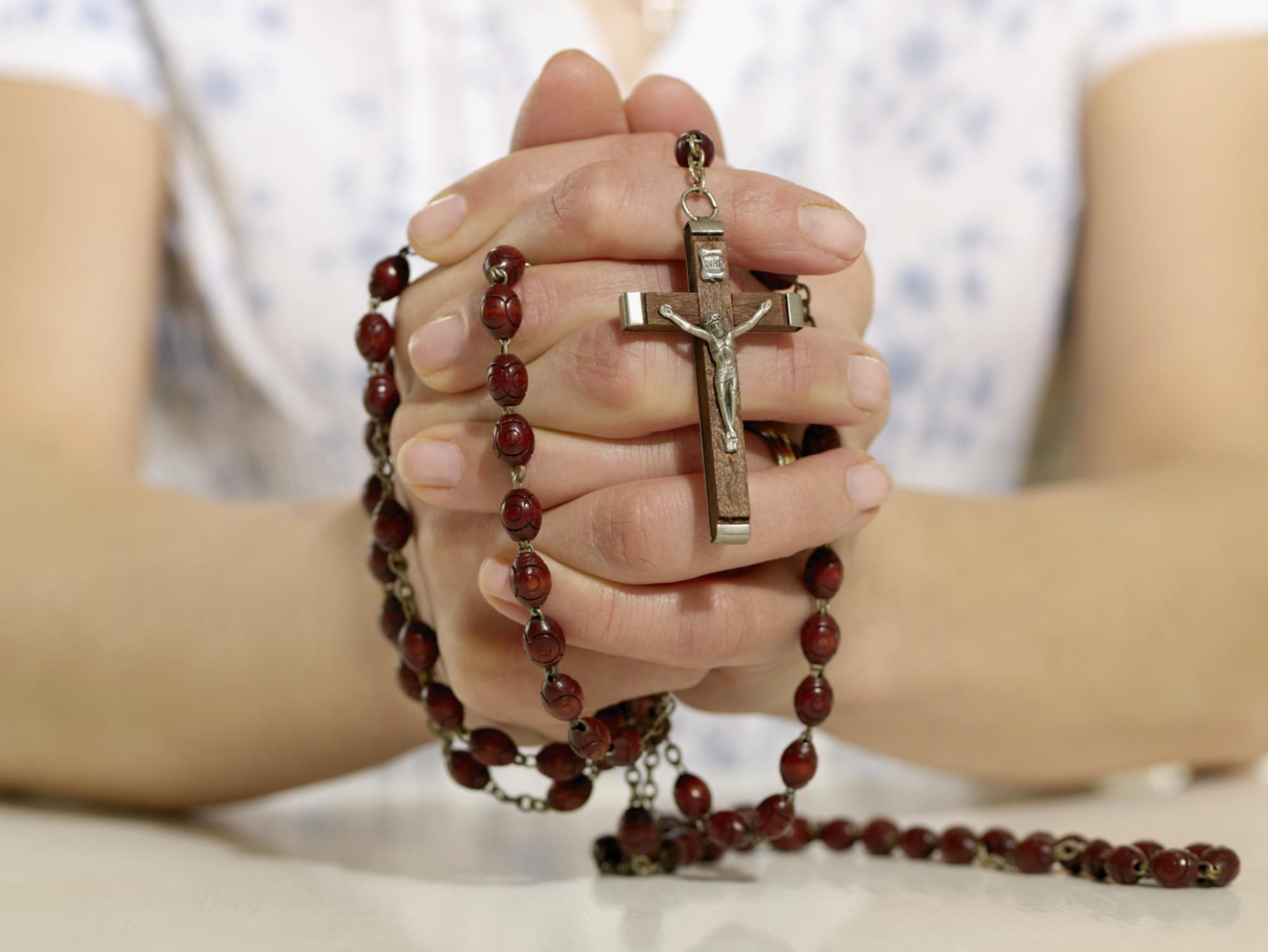 Red Rosary Wrapped Around Hands