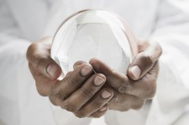 Close up of man's hands holding a crystal ball