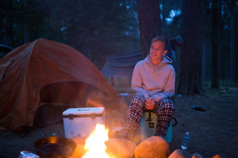 Teenage boy sitting beside camp fire