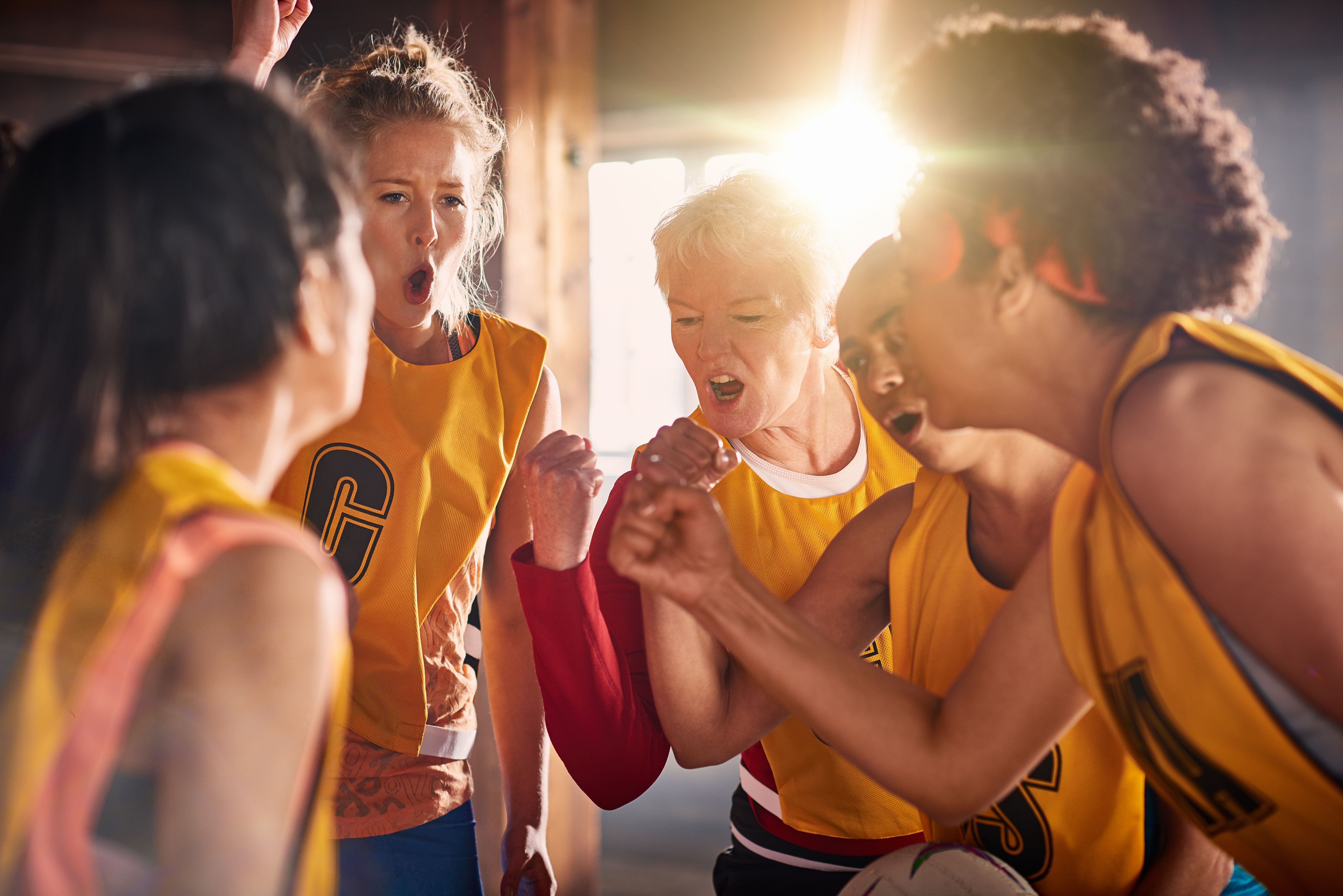 Female netball team preparing to training in gym.