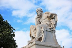 Statue of Socrates against partly cloudy sky.