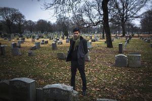 A man visiting a graveyard.
