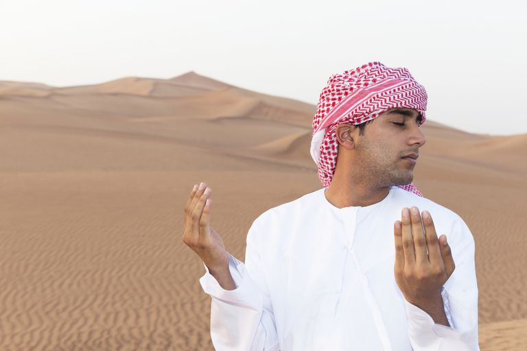 Arab man praying in the desert