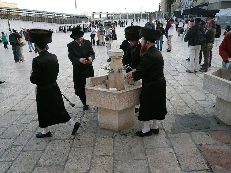 Four orthodox men washing their hands before shabbat prayers
