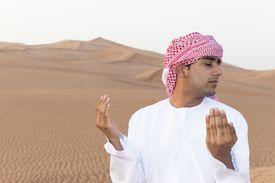 Arab man praying in the desert