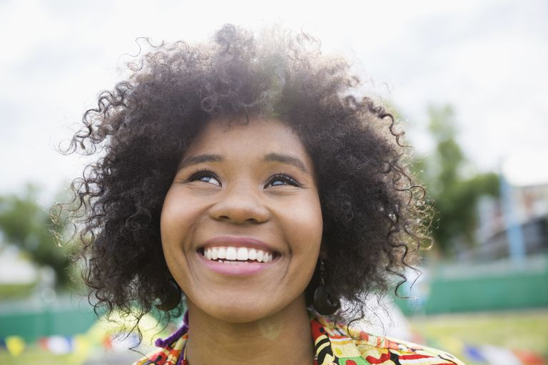 Portrait enthusiastic young woman with curly black afro looking up