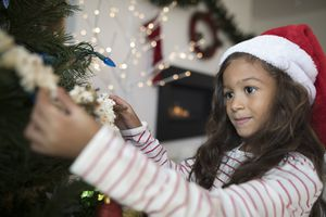 Focused girl in Santa hat hanging popcorn string decoration on Christmas tree