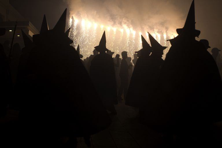 Group of witches wearing hats and cloaks in silhouette with fires burning.