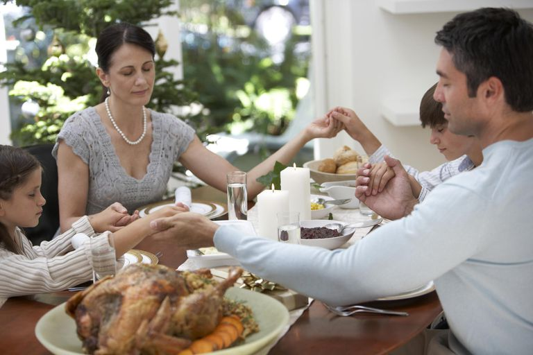 Family sitting around dinner table, holding hands