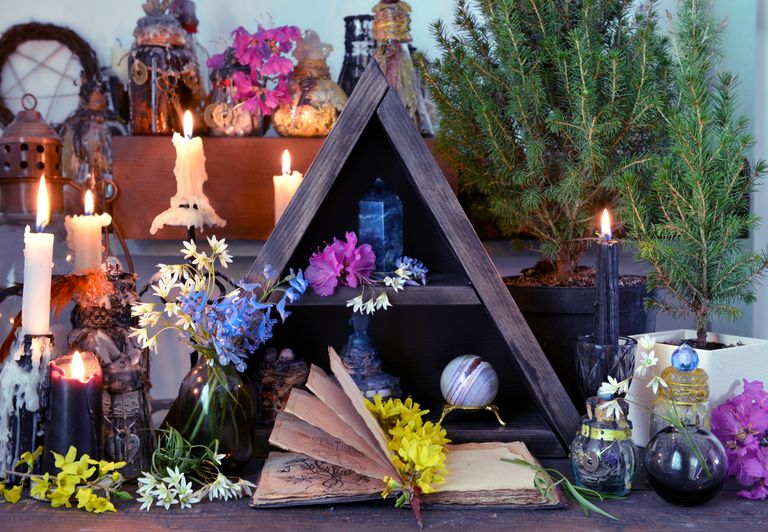 Open book with flowers, candles and magic bottles on witch table.