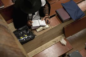 Jewish man with tefillin reading religious prayer book