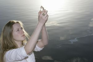 Young woman by lake holding up crystal