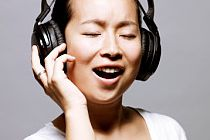 A woman with headphones singing
