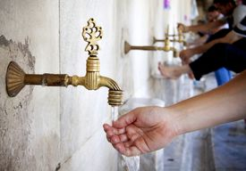 Men washing hands and feet in ablution faucets in the Sultan Ahmed Mosque, Istanbul (Turkey)