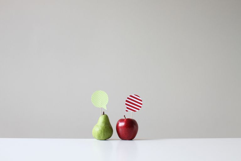 Conceptual apple and pear with speech bubbles