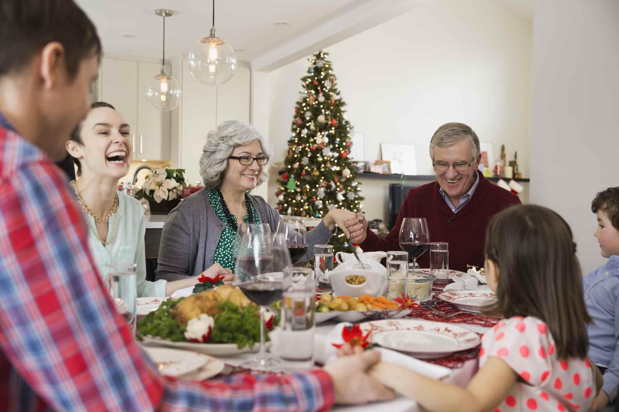 Multi-generation family saying grace before Christmas dinner.