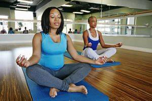 Two women meditating at a gym