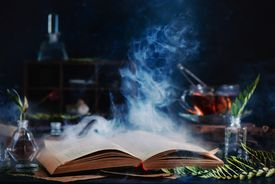 Open spell book with magical smoke