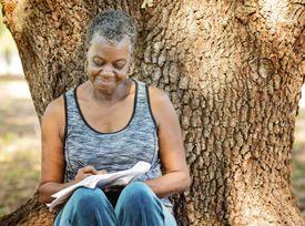 woman writing next to tree