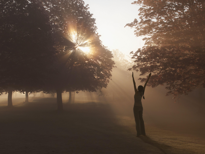 Woman practicing yoga in foggy field
