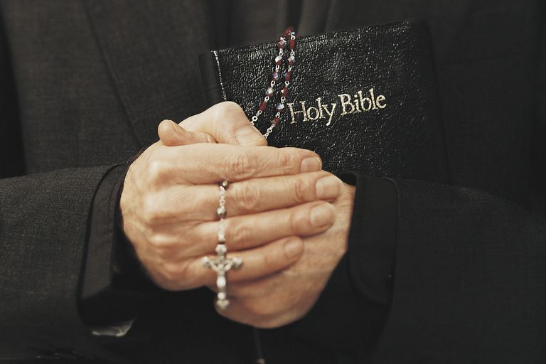 A Catholic priest holds a Bible and rosary