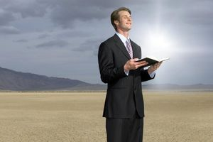 Young businessman in dry lake holding open book