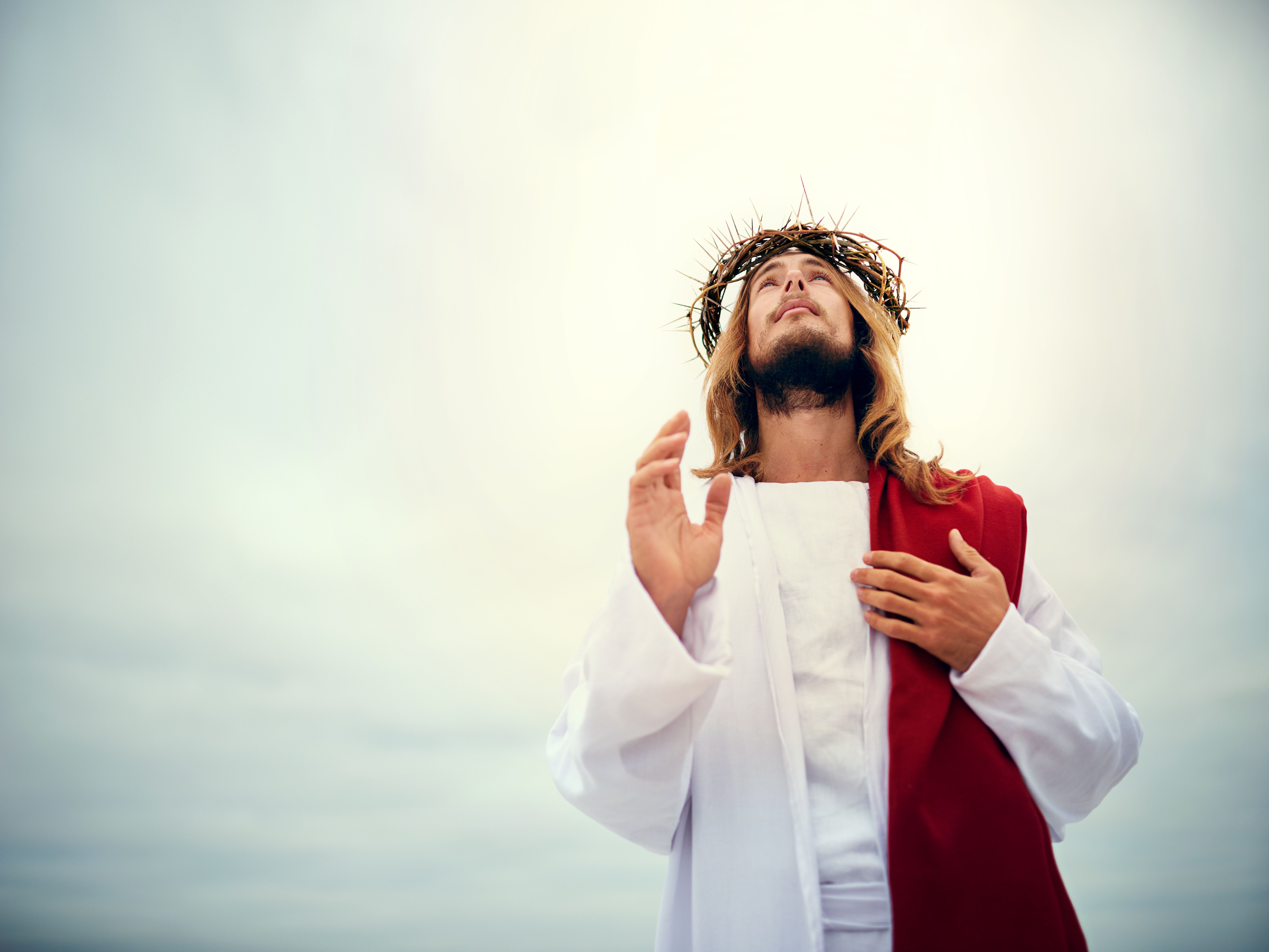 Man dressed a Jesus looking at the sky.