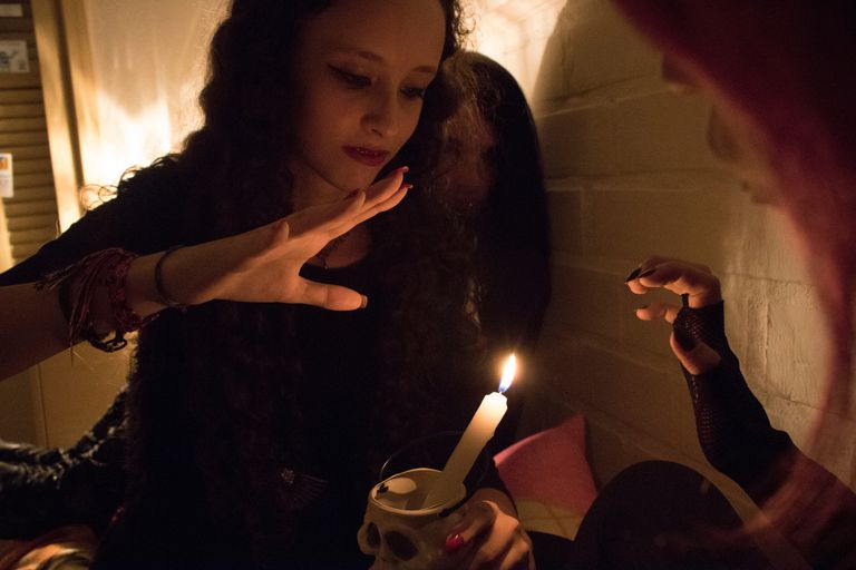 Friends Looking At Illuminated Candle During Wiccan Ceremony