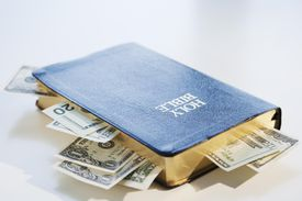 A bible with cash sticking out of it