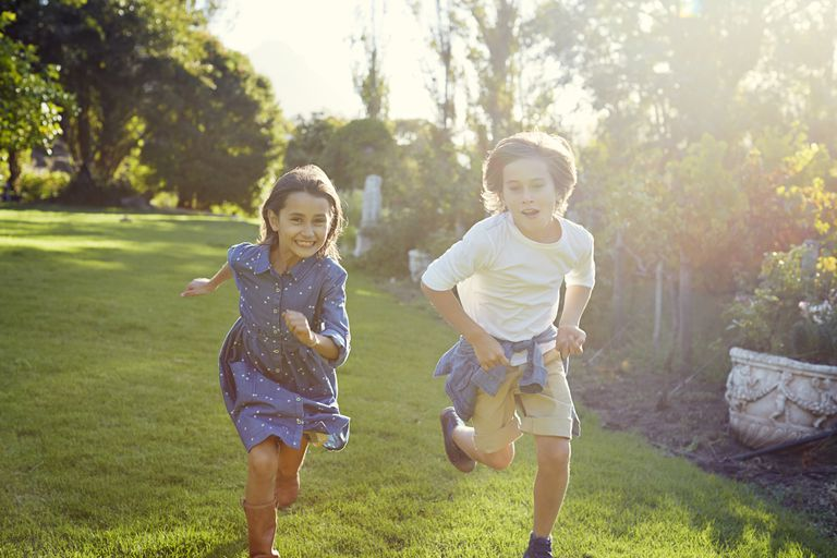 Two young children running in garden