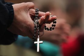 Person holding rosary beads.
