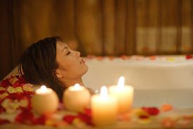 lady in a bathtub with rose petals and candles