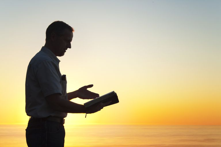 A man reviewing a book at sunset