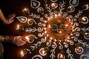 A woman arranges oil lamps during Diwali