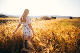 Retro style girl standing in golden wheat field at sunset