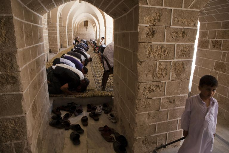 men kneel in mosque