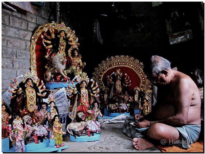 An artisan hand painting smaller idols