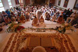 Sikh Bride and Groom Seated Before Guru Granth Sahib in Anand Karaj Wedding Ceremony
