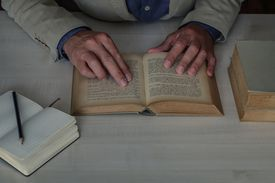 person reading old book on a desk