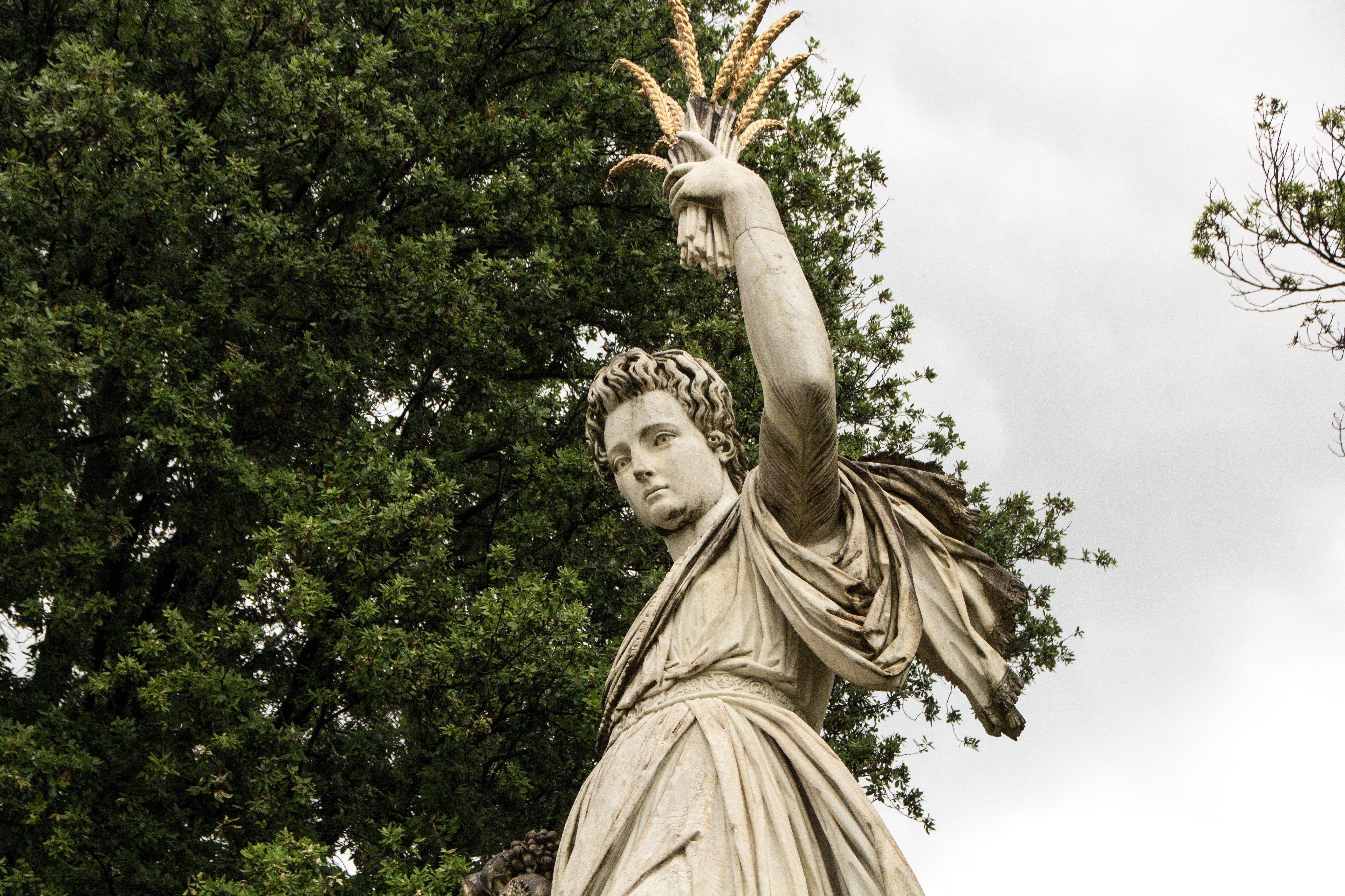 Statue of Abundance, in the Boboli Garden. Female sculpture in white marble with wheet bouquet of bronze.