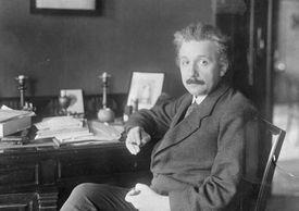 Physicist Albert Einstein seated at desk with cigarette.