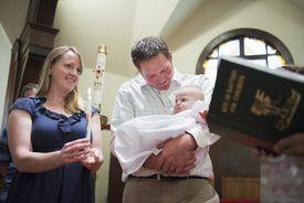 Caucasian parents having baby baptized in church