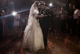 A Muslim Uyghur couple dance at their wedding