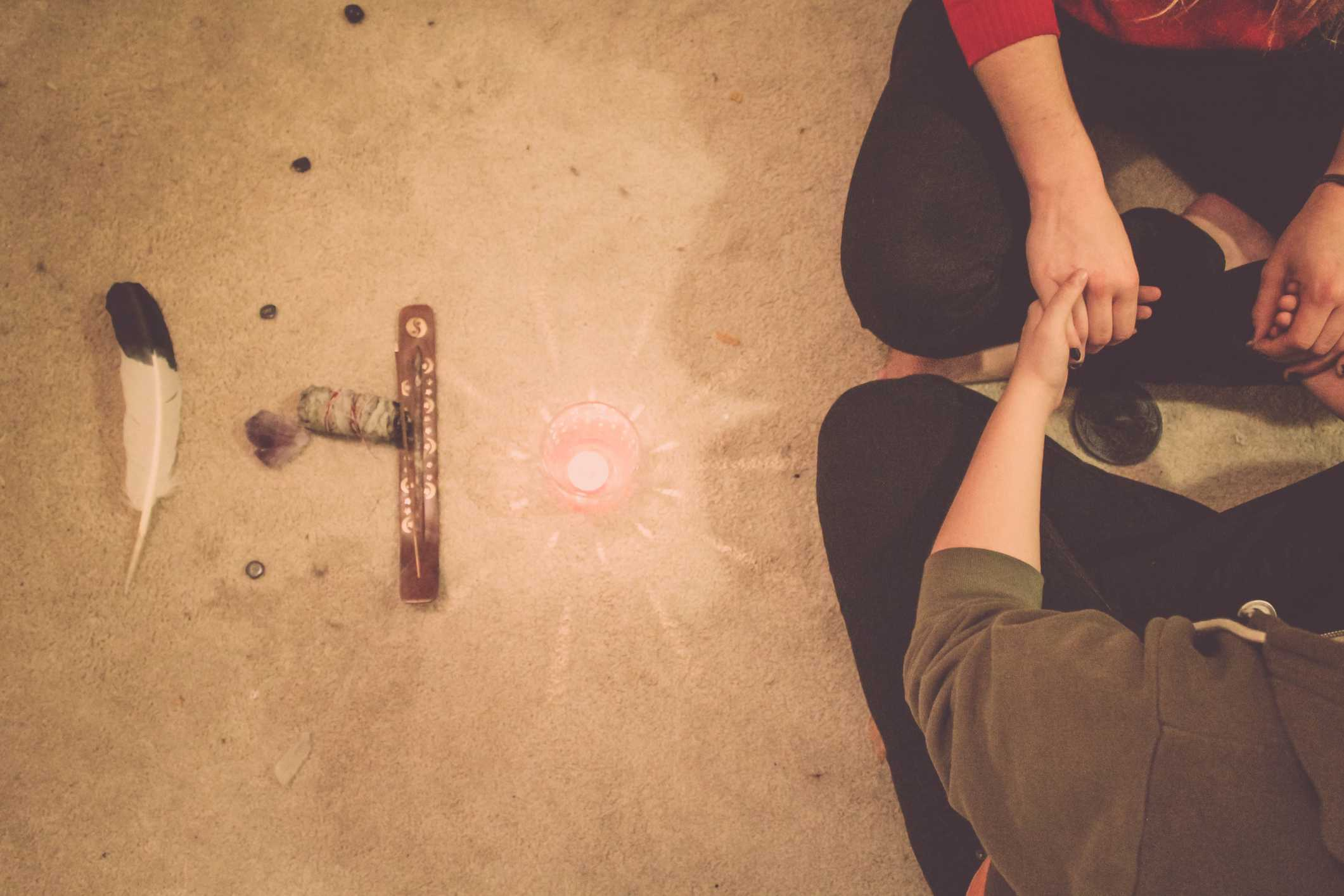Man And Woman By Tea Light Candle On Rug During Wiccan Ceremony
