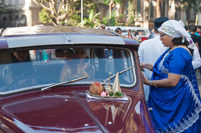 Parsi family performing puja for Morris vintage car