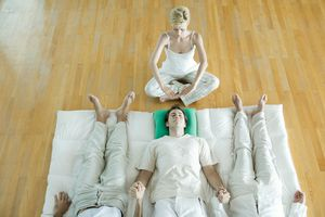 Alternative therapy session, three adults lying side by side, holding hands while therapist puts hands over man's head