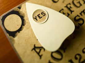 Ouija Board and planchette highlighting word yes, close-up